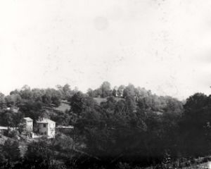 Toll cottage in foreground; LaBoiteaux property on hill in background.